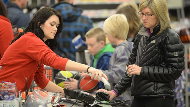 Cashier Brenna Otts, left, helps customers at the Sports Authority store in Front Range Village Friday morning Nov. 29, 2013.
