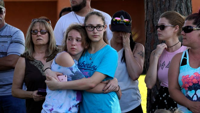 People comfort each other at a vigil outside Santa Fe High School where a gunman shot numerous people, killing 10 and injuring 10 others.