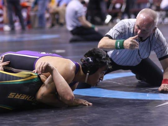 Kirtland Central's Keishaun Aspaas pins Pecos' Orlando Romero Friday in their 145-pound quarterfinal match during the 4A state tournament at the Santa Ana Star Center in Rio Rancho.