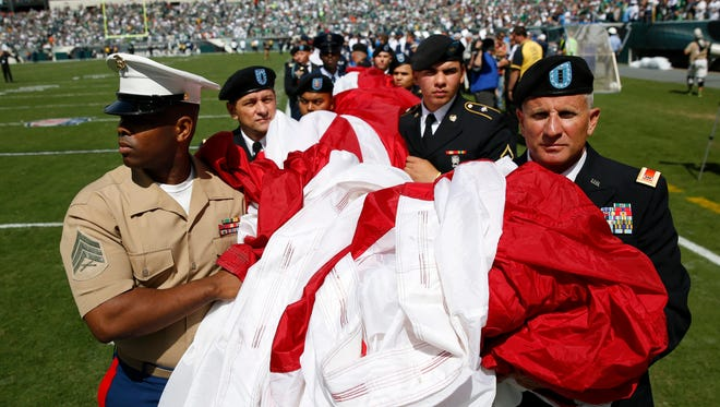 Military personnel carry an American flag on to the field in Philadelphia.