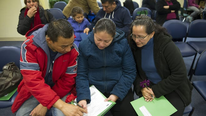 Jasmine Contreras, center, her husband Henry Valerio, left, and mother, Avida Flores, all from Dumfries, Va., fill-out a health care insurance application at the Greater Prince William Community Health Center, Evergreen Terrace Site, in Manassas, Va., Saturday, Nov. 15, 2014.