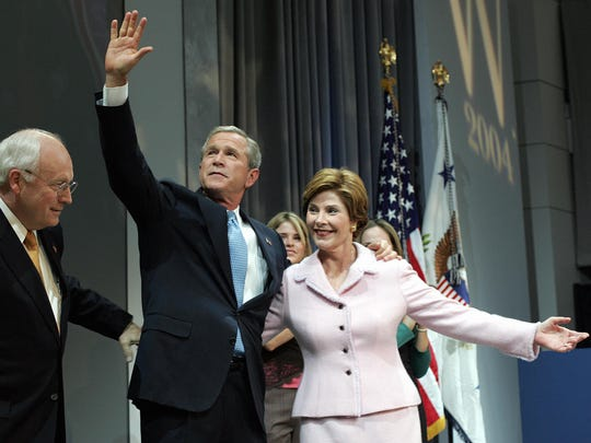 President George W. Bush (center) waves as he and his wife Laura are introduced ahead of his victory speech by Vice President Dick Cheney (left) on Nov. 3, 2004.
