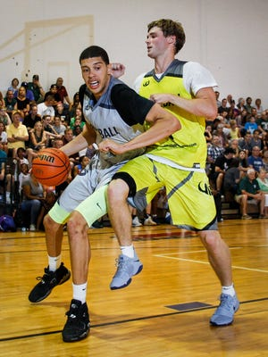Lansing Everett grad Trevor Manuel works his way into the paint against Tyler Johnson of Western Michigan, Thursday, July 6, 2017, during the Moneyball Pro-Am tournament at Aim High in Dimondale.