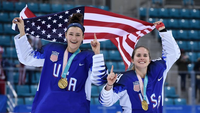 Megan Keller, left, holds the U.S. flag with teammate Danielle Cameranesi after winning gold in women's hockey during the Pyeongchang 2018 Winter Olympic Games on Feb. 22, 2018.