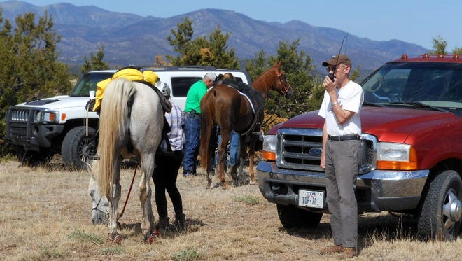 Fred Reed of the Sierra Blanca Amateur Radio Club communicates with other members at a veterinarian checkpoint during the Fort Stanton Endurance Ride.