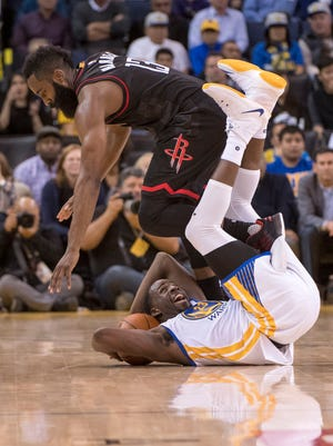 Houston Rockets guard James Harden (13, top) and Golden State Warriors forward Draymond Green (23, bottom) tangle after a jump ball call in a recent game.