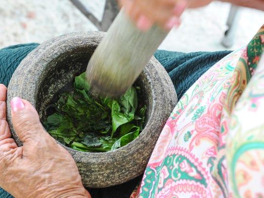 Rosalia 'Mama Rose' Mateo, demonstrates how leaves