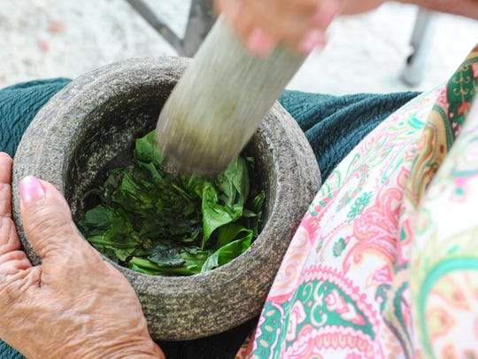 Rosalia 'Mama Rose' Mateo, demonstrates how leaves can be combined through pounding to produce traditional Chamorro medicine, while at the Sagan Kotturan Chamoru cultural center in Tamuning on Thursday, May 12.