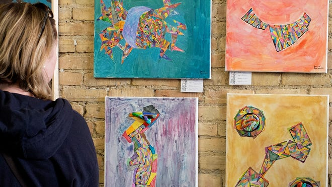 A woman looks at artwork by Sacha Roennecke on Sunday at Absolute Gallery in Lansing's Old Town.
