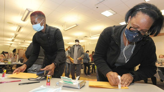 FILE - Amid the ongoing coronavirus pandemic, Simone Santiago, left, and Michelle Woods, both wearing face coverings, use glue to seal their envelopes during early voting at the Westgate Mall in Brockton, on Saturday, Oct. 17, 2020, for the November general election.