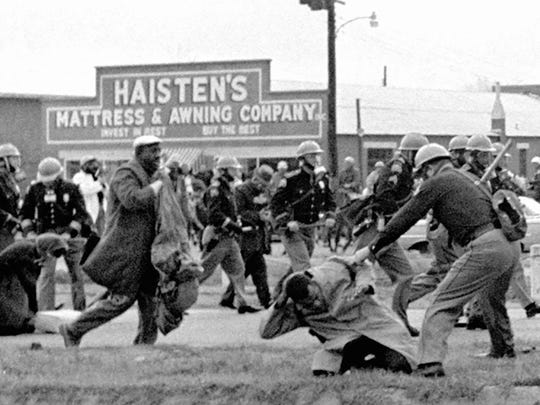 Alabama state troopers try to break up a voting march in Selma, Ala., in 1965. John Lewis, front right, now a congressman, is put on the ground.