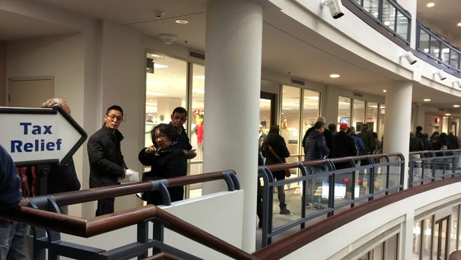 The line on Dec. 27, 2017, to pay 2018 property taxes in advance stretched out the doors of the Fairfax County tax office in Fairfax, a Virginia suburb of the District of Columbia.