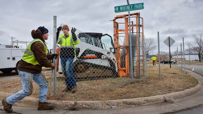 A crew from Boundary Fence and Design, Rice, works to install a cyclone fence Thursday morning, March 17, at the edges of Whitney Park on the site for what will become the new aquatic center.