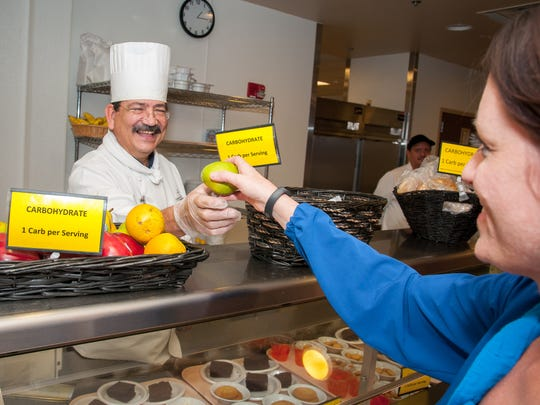 Food Service Manager Martin King hands a pear to Director