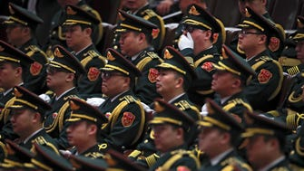 A member of military music band yawns while others watch the oath taking ceremony during a plenary meeting of China's National People's Congress at the Great Hall of the People in Beijing on March 18, 2018. China's ceremonial legislature appointed Chinese Premier Li Keqiang, the No. 2 leader of the ruling Communist Party, to a second five-year term Sunday and approved the appointment of a director for a new anti-corruption agency with sweeping powers.