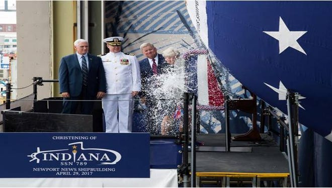 """Ship's """"sponsor"""" Diane Donald christens the Virginia-class submarine USS Indiana, witnessed by, from left, Vice President Mike Pence, Indiana Commander Jesse Zimbauer andNewport News ShipbuildingPresident Matt Mulherin, along with an audience of nearly 4,000 event guests, in April 2017 in Newport News, Virginia."""