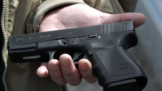 Firearms owner John Markell holds a Glock 9 mm pistol in Roanoke, Va., in this April 2007 file photo. In Michigan, state lawmakers including Rep. Luke Meerman, R-Allendale, have called for changes to the ways the state penalizes individuals who commit crimes while carrying guns.