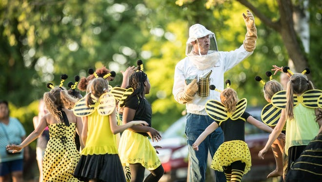 """Nathan Wesselowski portrays a beekeeper, with children as his bees, in """"Handel's Bestiary."""""""
