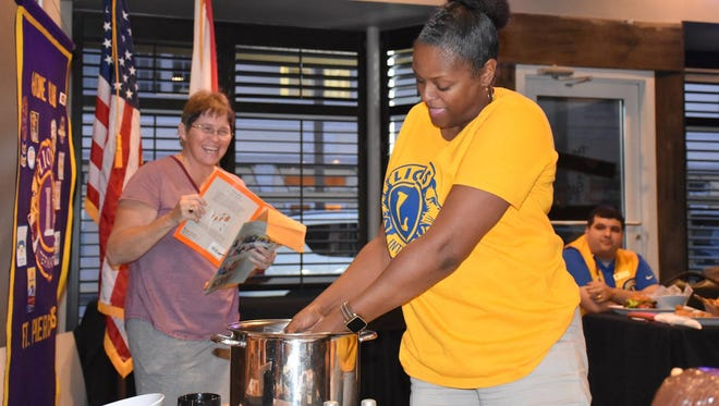 Lions Club member Jenny Champagne, right, adds to the Stone Soup, while storyteller Wendy Dwyer looks on.