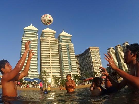Niños juegan con una pelota en la playa de Acapulco.