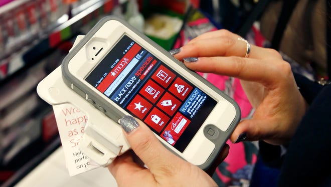 "In this Friday, Nov. 23, 2012, file photo, Tashalee Rodriguez, of Boston, uses a smartphone app while shopping at Macy's in downtown Boston. Shoppers are flocking online Monday, Nov. 28, 2016, as ""Cyber Monday"" sales hit their peak."