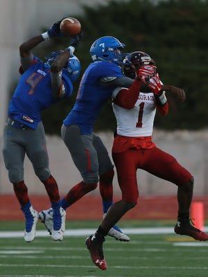 Americas' defensive back Randall Walker, left, intercepts a pass intended for El Dorado receiver Tyquez Hampton, right, during the second quarter Friday. Americas' James Gregg covers Hampton.