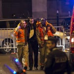 Wounded people are evacuated from the Stade de France in Paris on Nov. 13, 2015.