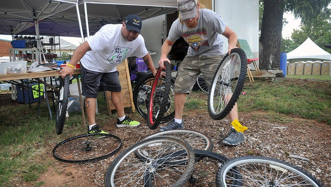 Rodney DeLaRoza, left, and Dwayne Polvado sort rims at the DLM Services tent at the Hotter 'N Hell Hundred Consumer Show Thursday. Polvado's business sells a wide variety of new and used bicycle parts.