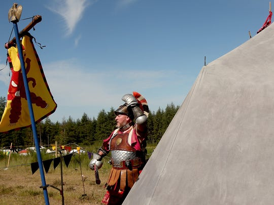 """Craig """"Idomeneus"""" Gehlert adjusts his helmet as he exits a tent and prepares to compete in the heavy combat tournament  during June Faire in Bremerton."""