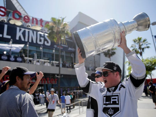 Los Angeles Kings fan Tim Bressler, right, of Newport Beach, Calif., carries a trophy in front of the Staples Center before the Kings face the New York Rangers in Game 5 of the Stanley Cup Final series Friday, June 13, 2014, in Los Angeles. (AP Photo/Jae C. Hong)