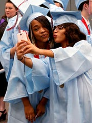 Sharin Beatty (left) and Mireya Chavez pose for a photo before the Hirschi graduation ceremony Saturday afternoon at the Multi-Purpose Events Center.