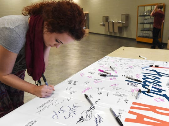 Mountain Home High School senior Rheagan Hill signs a a a banner Wednesday for Rachel's Challenge, a program on the importance of spreading kindness .