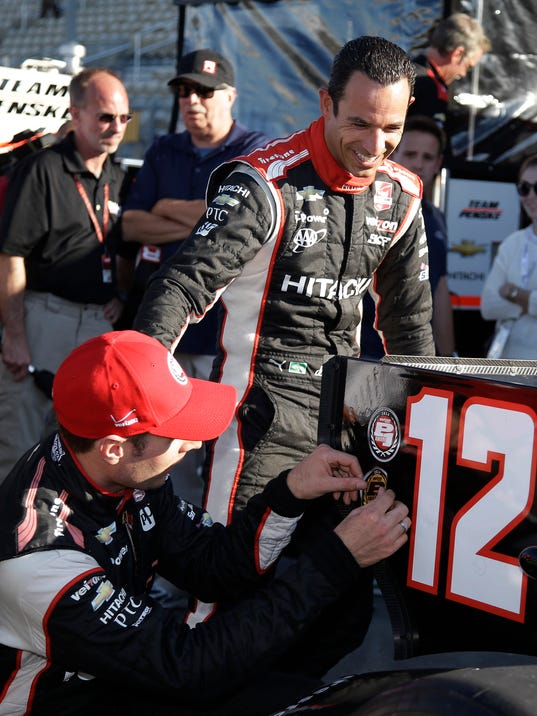 Will Power, left, of Australia, is greeted by teammate Helio Castroneves, of Brazil, after qualifying for the IndyCar auto race Saturday, Aug. 23, 2014, in Sonoma, Calif. Power won the pole position and Castroneves qualified in sixth. (AP Photo/Eric Risberg)