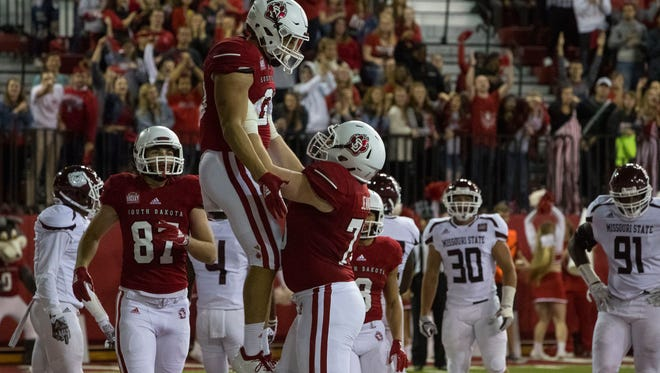 University of South Dakota's Ben Klett (30) celebrates with teammates after scoring a touchdown during a game against Missouri State, Saturday, Oct. 6, 2018 in Vermillion, S.D.