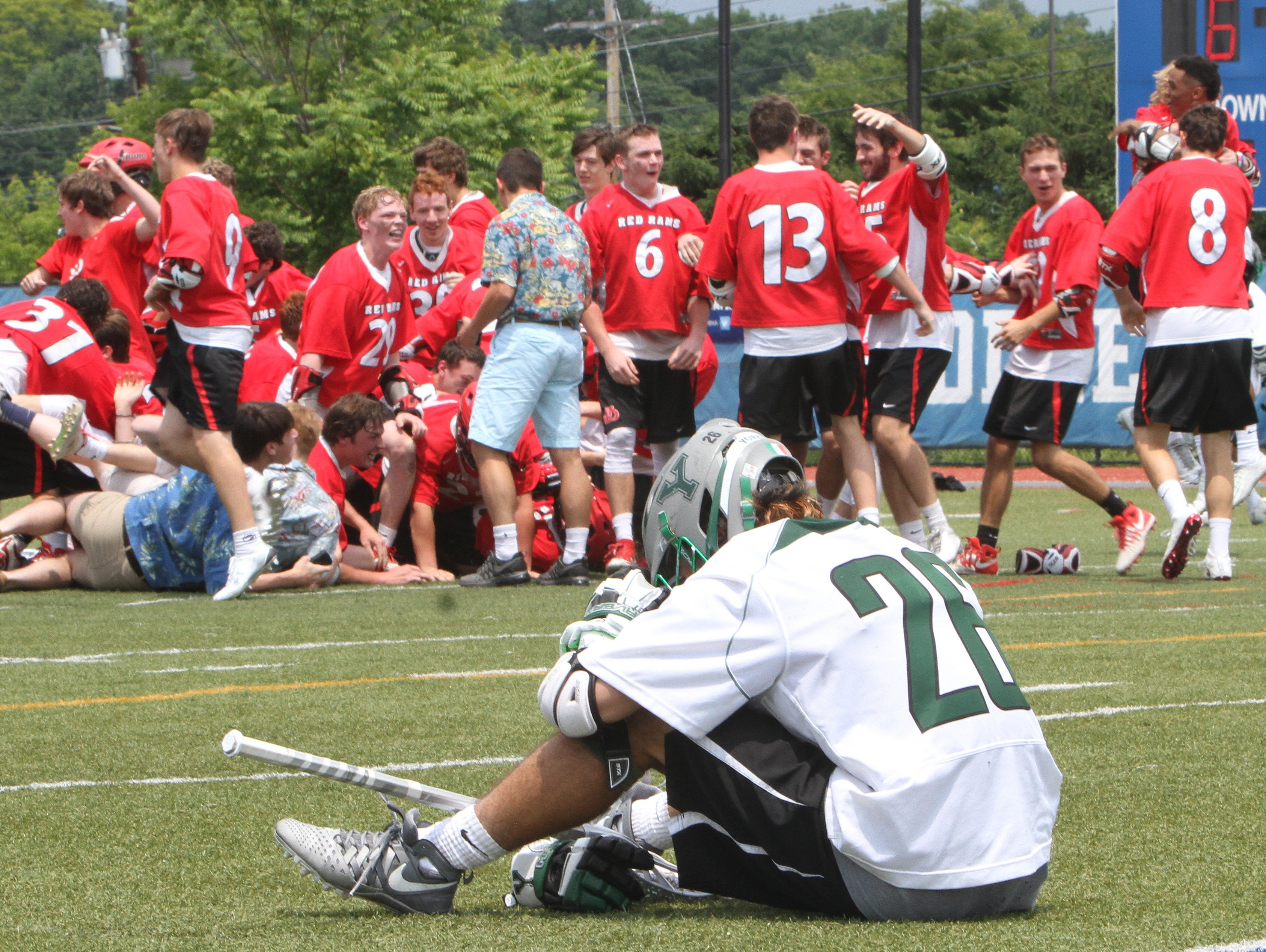 Yorktown's Dom Cioffi (26) sits on the field as Jamesville-Dewitt players celebrate their 9-6 victory in NYSPHSAA Class B championship lacrosse game at Middletown High School June 11, 2016.