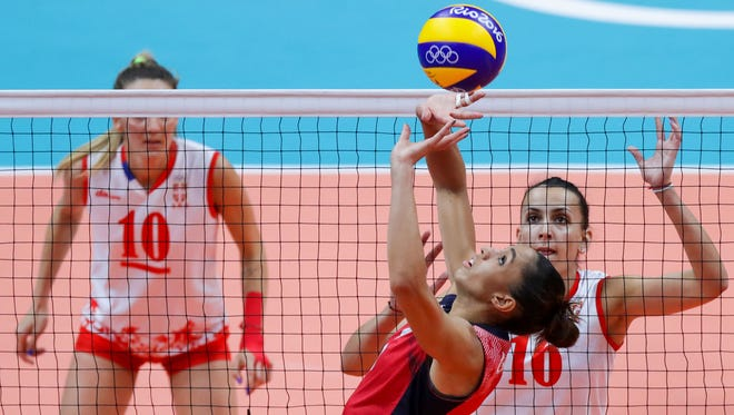 The USA's Alisha Glass (1) prepares to set up a teammate with Serbia middle blocker Milena Rasic looming.