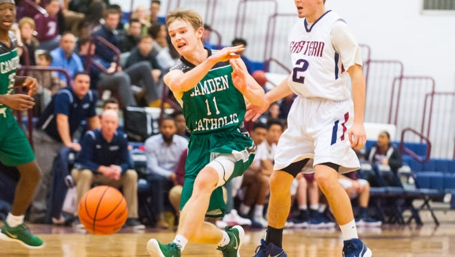 Camden Catholic guard Pat Corbett, left, passes up court against Eastern in a season-opening 50-48 road win over the Vikings on Friday night.