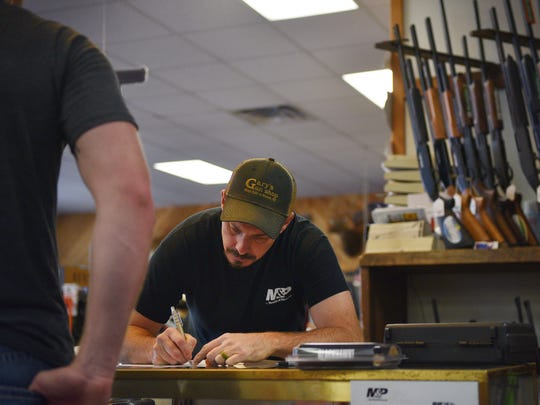 Manger at Gary's Gun Shop, Anthony Naatjes, writes down information after a gun purchase at the store Friday.