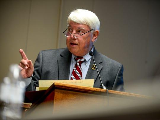 Jimmy Eldridge speaks at the podium at a board meeting