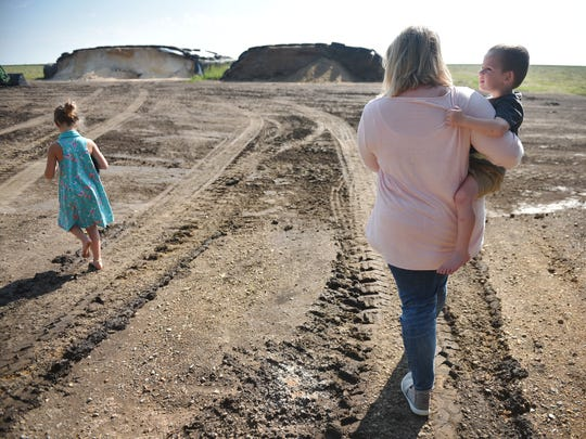 Morgan Kontz and her daughter Elliette, 6, and her son Elijah, 3, walk around their farm Wednesday, Aug 8, in Colman. Morgan Kontz and her husband run the family farm. They both work on the farm full time.