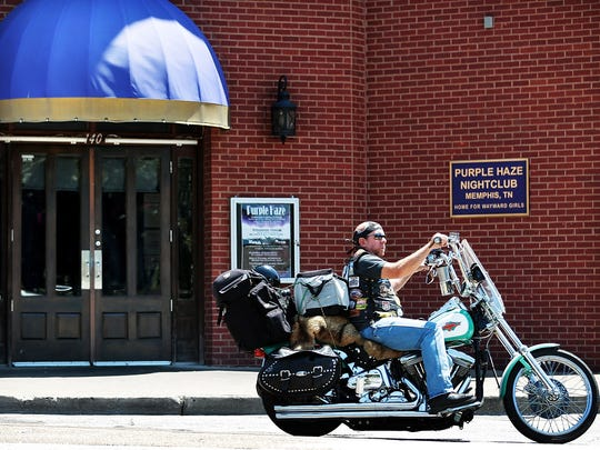 A motorcyclist passes the Purple Haze on Second Street which is embroiled in a lawsuit with the nearby Club 152. Purple Haze nightclub owners believe that they should be able to serve alcohol till 5 a.m. like neighboring clubs around the corner on Beale.