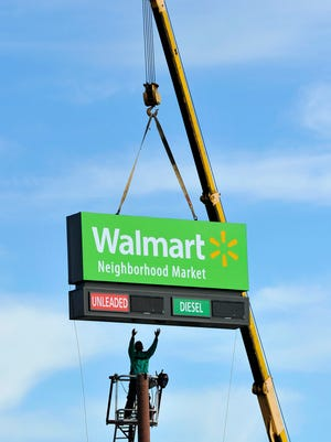 A worker stretches his arms to guide a sign into position on top of its pole Friday, Jan 15, 2016, at the new Wal-Mart Neighborhood Market location on Old Jacksonville Road in Tyler, Texas. The Bentonville, Ark., company announced Friday the planned closure of 269 stores, more than half of them in the U.S. and another big chunk in its challenging Brazilian market.