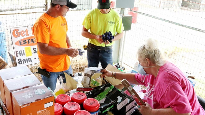 Karen Jones, bottom right, helps Berry McHenry, left, and Billy Smith pick up some small clamps, Friday, July 10, 2020, at the GetRDunn pre-auction sale at the Hugh Hardin Arena in Kay Rodgers Park. Tim Dunn, owner, will hold a public auction for items ranging from boxes of screws and tools to salvaged and wholesale products, Saturday, July 11, 2020, at 10 a.m. in the arena.