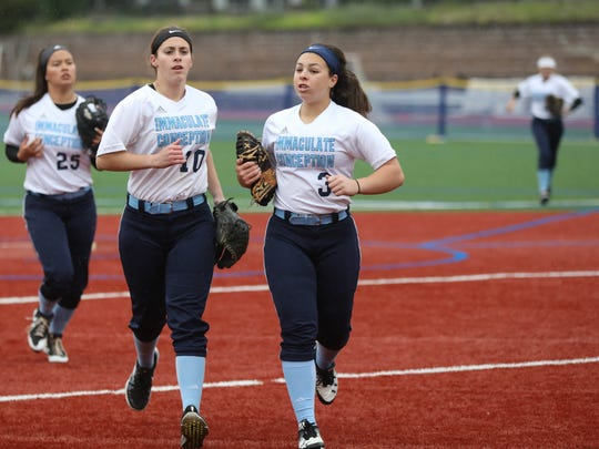 Christina Braid (3), Jaden Farhat (10) and Kayla Robert (25), all of Immaculate Conception, run off the field after the game was called due to rain after one inning of play.  The game will continue in the second inning on Monday. Sunday, May 13, 2018