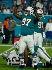 Miami Dolphins defensive tackle Jordan Phillips (97) celebrates after sacking New England Patriots quarterback Tom Brady (12), during the first half of an NFL football game, Monday, Dec. 11, 2017, in Miami Gardens, Fla. (AP Photo/Wilfredo Lee)