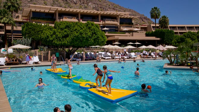 Patrick Breen/The Republic Kids try to keep their balance on a waterline course at one of the nine pools at the Phoenician resort in Phoenix. Kids play in the pool in front of the rooms inside the Phoenician resort in Scottsdale, AZ, on Sunday, April 20, 2014.