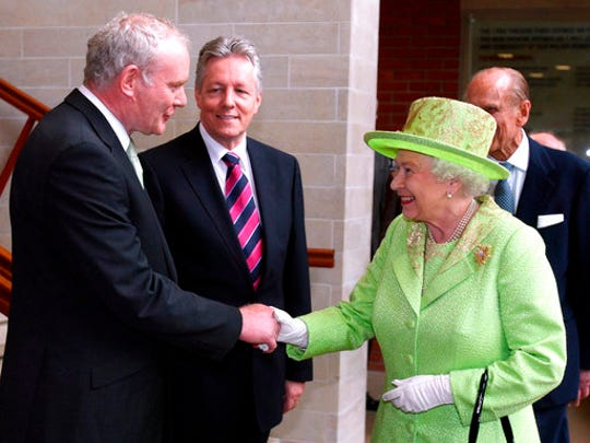 FILE - In this June 27, 2012 file photo Britain's Queen Elizabeth II shakes hands with Northern Ireland Deputy First Minister and former IRA commander Martin McGuinness watched by First minister Peter Robinson, centre, at the Lyric Theatre in Belfast, Northern Ireland. McGuinness, the Irish Republican Army commander who led his underground, paramilitary movement toward reconciliation with Britain, and was Northern Ireland's deputy first minister for a decade in a power-sharing government, has died, his Sinn Fein party announced Tuesday, March 21, 2017, on Twitter. He was 66.