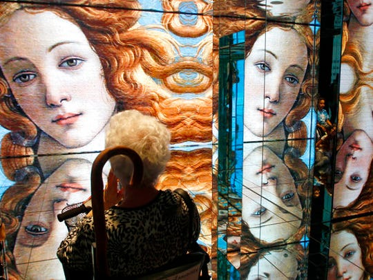 """In this Friday, June 5, 2015 file photo a person visits the Italian pavilion as Sandro Botticelli's mid 1480s painting of Birth of Venus is displayed on the walls at the Expo 2015 in Rho, near Milan, Italy. A new exhibition of Italian Renaissance master Sandro Botticelli's paintings opens this weekend in Boston, """"Botticelli and the Search for the Divine"""" at Boston's Museum of Fine Arts."""