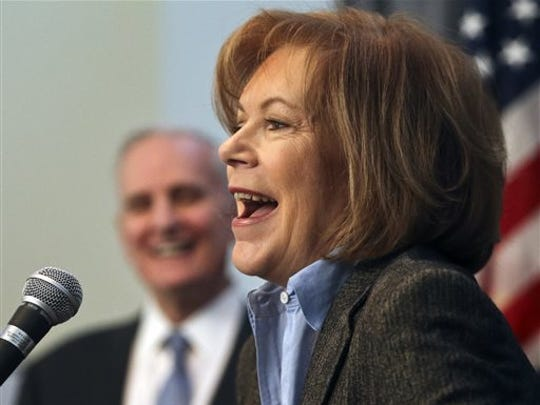 Lt. Gov. Tina Smith speaks as Gov. Mark Dayton looks on in this file photo from 2014.