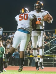 Woodrow Wilson wide receiver Fadil Diggs (17) celebrates a two-point with lineman Shatese Shields (50) against Moorestown at Moorestown High School on Friday, October 6.